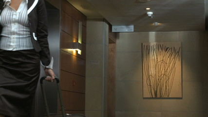 LS PAN OF A BUSINESSWOMAN WALKING OUT OF A LIFT