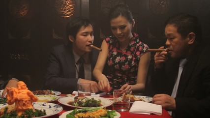Businessmen drinking and smoking in Chinese restaurant with female on lap