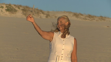 MS PAN OF A MATURE WOMAN HOLDING A STARFISH