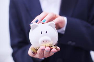 Business woman saving money in a piggybank