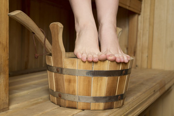 Beautiful female feet in sauna, bath accessories