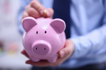 Businessman putting coin into small piggy bank