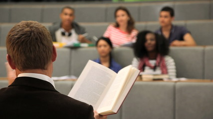 Teacher in front of students in lecture theatre reading literature