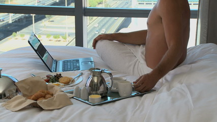 LS PAN OF A BUSINESSMAN IN A TOWEL HAVING BREAKFAST AND WORKING IN HIS HOTEL ROOM