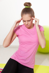 Woman suffering from headache during workout