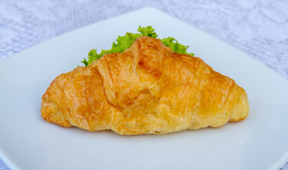 Sandwich croissant with vegetable on white plate.