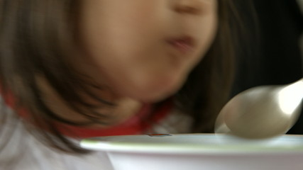 Little girl eating a soup, mouth close up