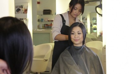 WS, Female client sitting in hairsalon, Hairstylist putting on cape