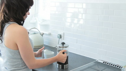 Female pouring coffee from french press into cup