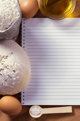 Notebook on the table with the dough, flour and eggs