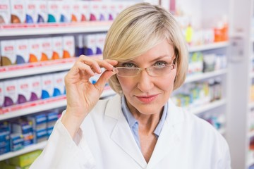Smiling pharmacist holding her glasses
