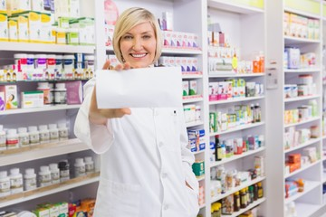 Smiling pharmacist showing paper at camera