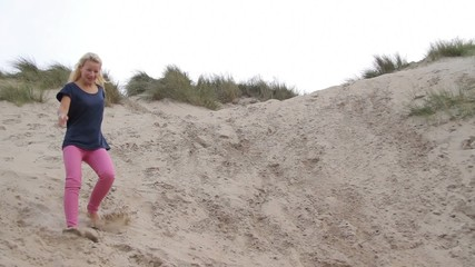 Teenagers running down the dunes