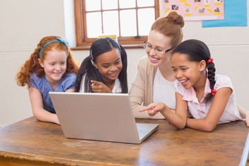 Teacher and pupils looking at laptop