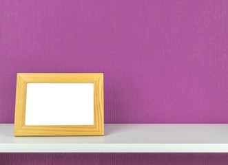 A blank picture frame on a shelf with copy space background