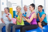 People working out with dumbbells in gym class - 79613907