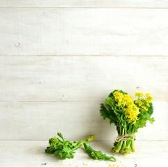 菜の花の花束(菜の花の一種) 白木材背景