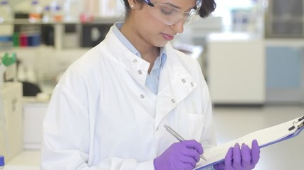 Portrait of Female writing down notes on notepad in science laboratory and looking to camera