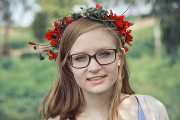 Cute teenage girl with glasses and a wreath of spring flowers