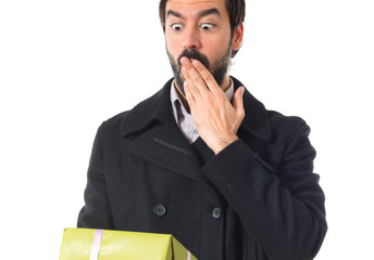 Surprised man holding a gift