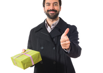 Man holding a gift with his thumb up