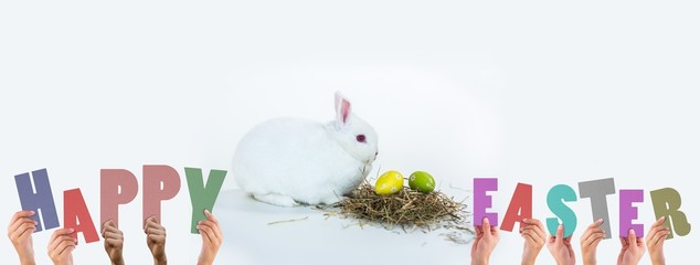 Composite image of hands holding up happy easter