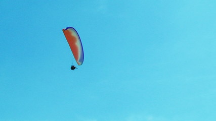 Several Paragliders Soaring In Blue Sky
