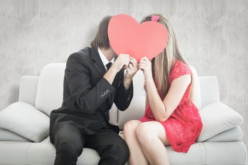 Cute geeky couple kissing and holding heart over faces