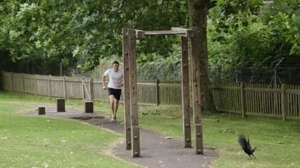 Male running up to parallel bar and exercises