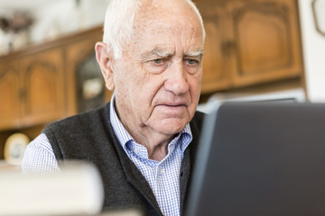 Senior man looking for information in books and internet