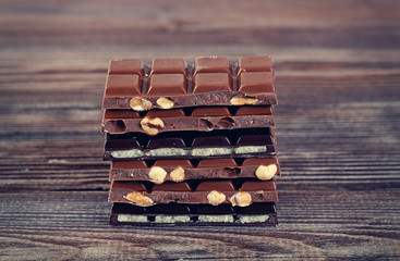Stack of dark and milk chocolates on wooden table