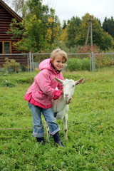 Happy girl embracing a white goat at the green pasture