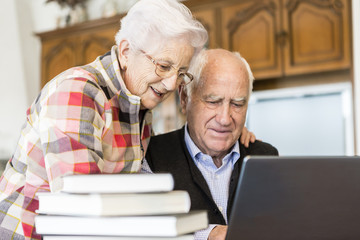 Senior couple looking for information in books and internet