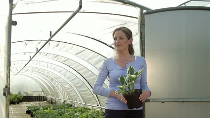 Portrait of female holding plant in front of green house