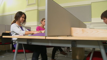 Female typing on laptop on other female looking over shoulder