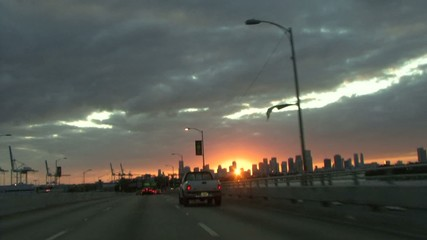 Driving along bridge towards miami city at sunset