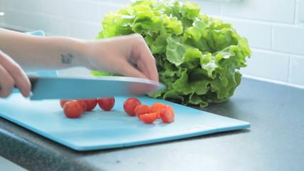 Female tomato's and preparing salad in kitchen