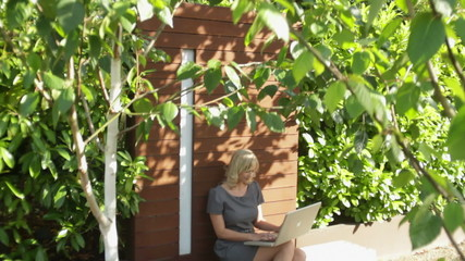 Dolly shot, wide shot of female on bench in garden working on laptop