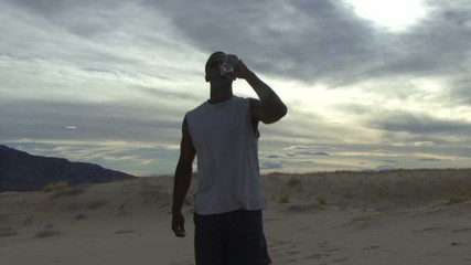 Male drinking water in desert