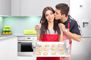 Young couple baking cookies in a kitchen