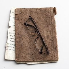 glasses and old notebook on table