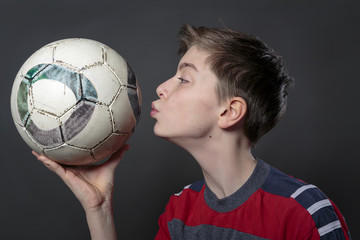 funny teenage boy is kissing a soccer ball, with gray background