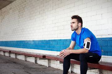 male athlete sitting on the bench and looking far away