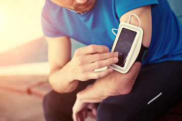 athlete listening to music on armband for smartphone