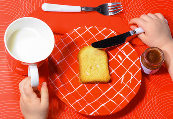 little hands eating a bread and drinking milk.