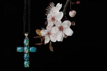 Gemstone cross on flowering tree branch