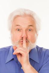 Elderly man with finger on lips