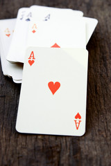 Deck of cards on wooden background (ace of heart)