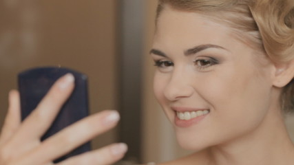 Girl with make-up looks at herself in a mirror