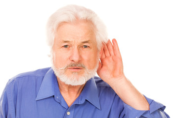 Elderly man holds hand on ear